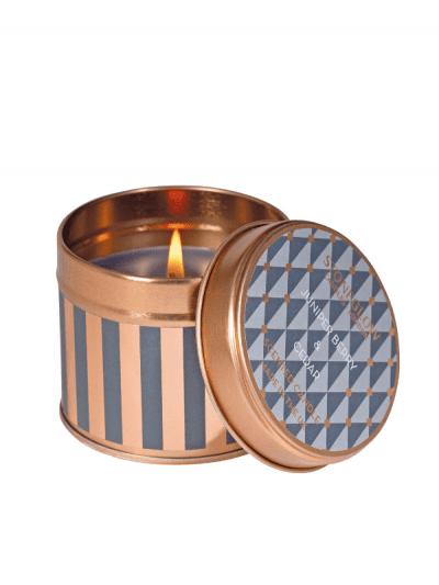 StoneGlow - juniper & cedar candle in a tin, flame is burning