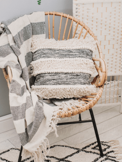 Black and white striped cushion on a wicker chair in a home