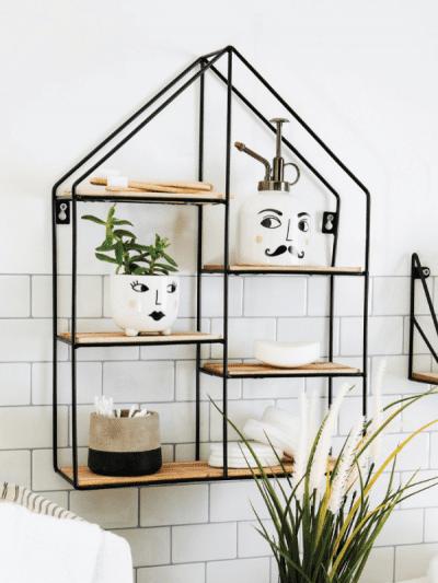 black shelf unit in a house shape, in bathroom