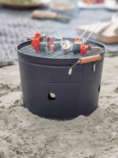 Black bucket BBQ on the beach with vegetable skewers grilling