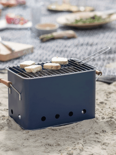 Blue square bucket BBQ on the beach with food grilling